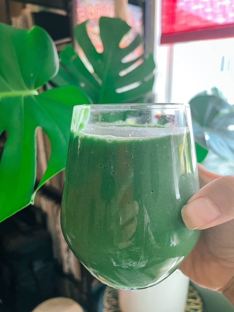 green smoothie being held in front of Monstera plant